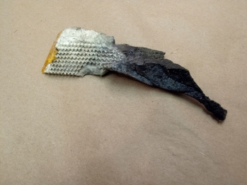 "2 (no.1). 2 found objects (road reflector, road tar), glue, paint. approx. 4""x1"", 2013"
